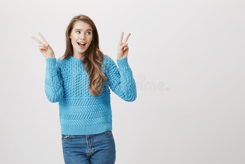 A mulher alegre com a expressão positiva que levanta as mãos e que mostra a vitória ou a paz gesticula, olhando de lado ao cantar imagem de stock