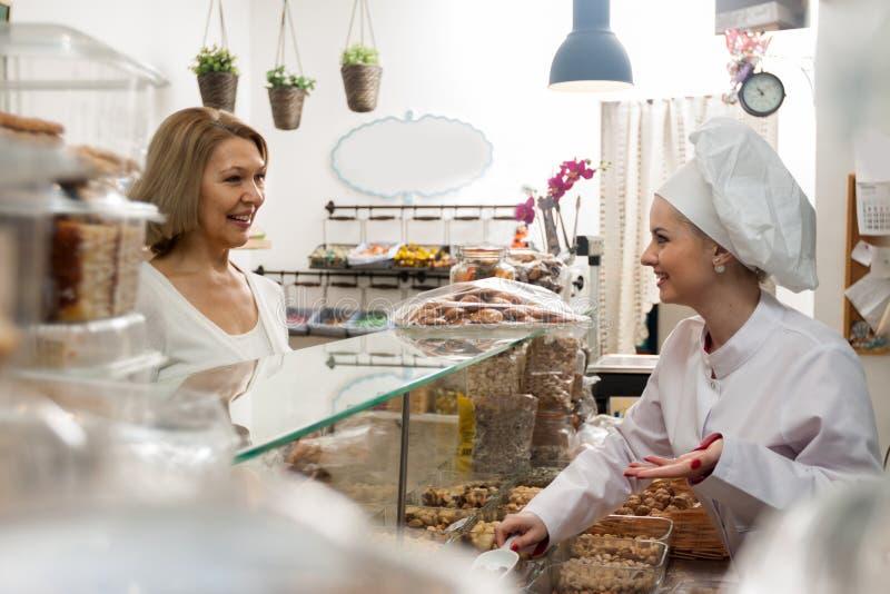 Mulher alegre da loja que oferece porcas e o smilin femal maduros do cliente fotografia de stock royalty free
