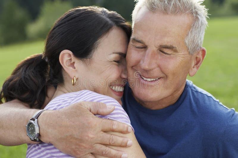 Mulher alegre de abraço do homem superior foto de stock