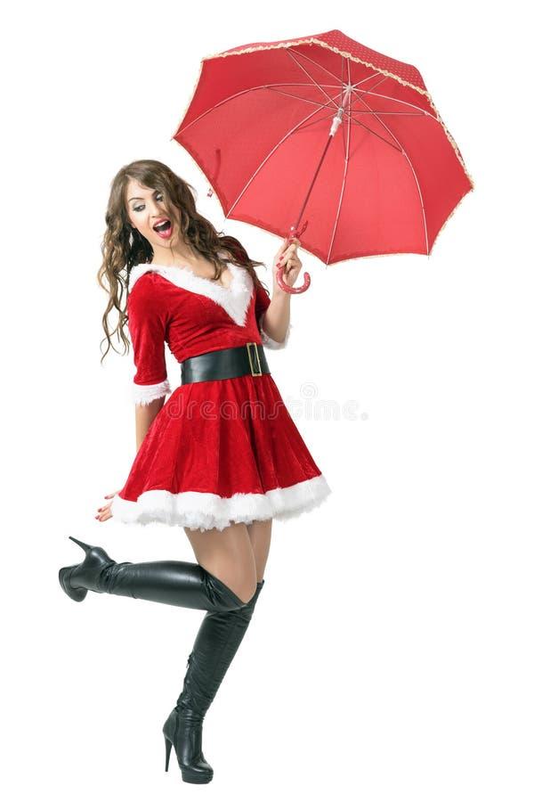 Mulher alegre de Santa que guarda o guarda-chuva que salta no meio do ar imagens de stock