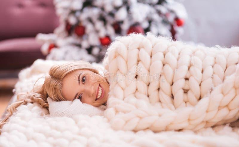 Mulher alegre de sorriso que encontra-se sob uma cobertura morna foto de stock
