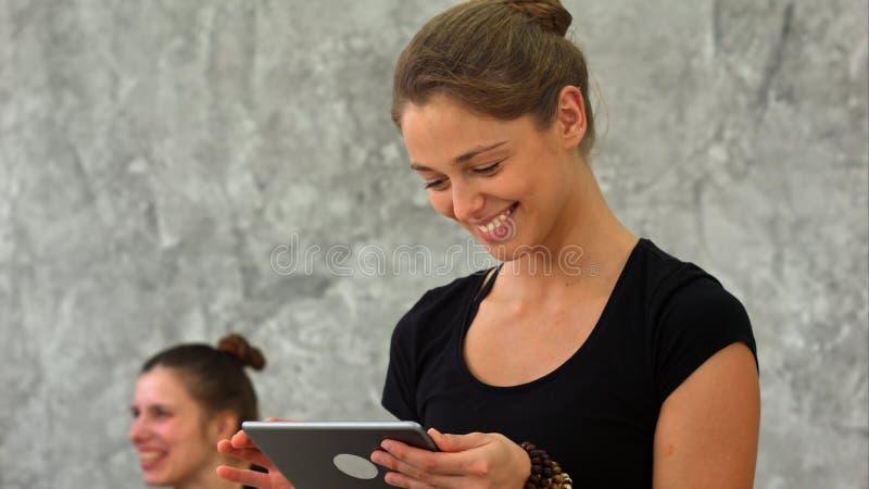 Mulher alegre desportiva que texting na tabuleta na sala brilhante durante a classe da ioga fotos de stock royalty free