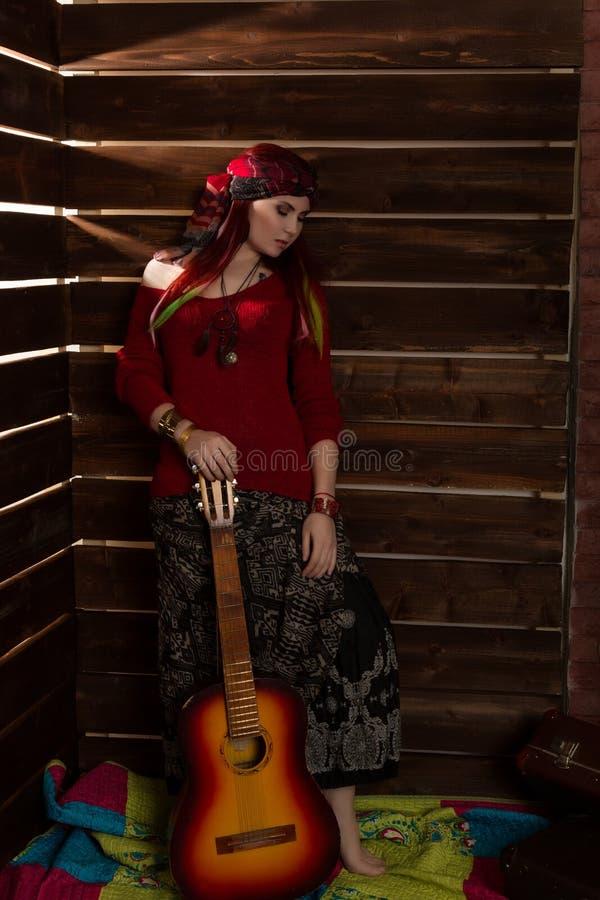 Mulher alegre do ruivo do boho da hippie que está com guitarra em um fundo de madeira da parede imagem de stock