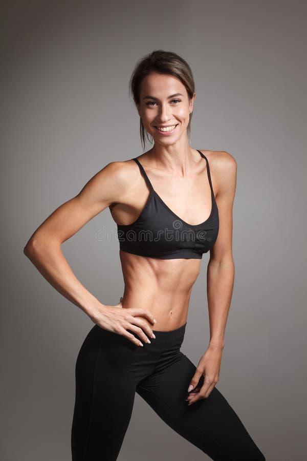 Mulher alegre e sorridente, com uma postura, com um fundo neutro de estúdio isolado fotos de stock royalty free