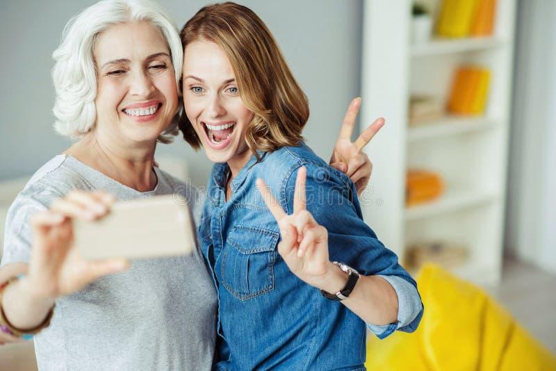 Mulher alegre e sua filha que fazem selfies foto de stock royalty free