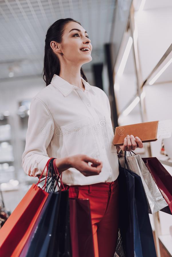 A mulher alegre está comprando coisas no boutique isento de direitos aduaneiros foto de stock