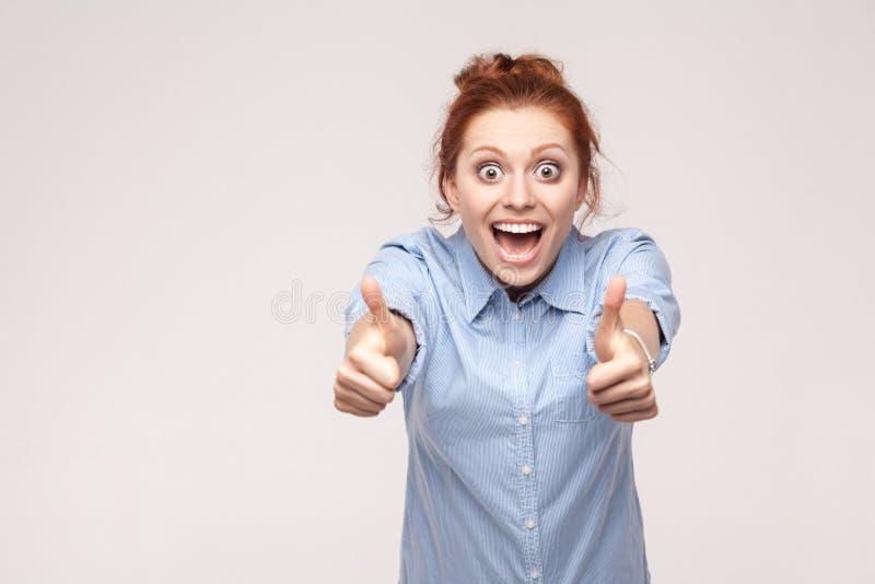 Mulher alegre feliz do ruivo que mostra o polegar que olha acima a câmera imagens de stock royalty free