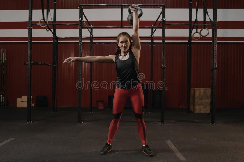 Mulher alegre forte com o corpo muscular que exercita com kettlebell quando treinamento do crossfit imagens de stock royalty free