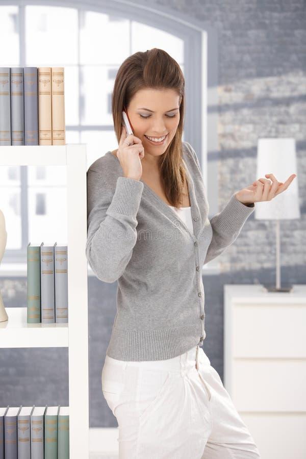Mulher alegre no atendimento de telefone em casa foto de stock royalty free