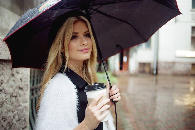 Mulher alegre no café bebendo da manhã da rua foto de stock