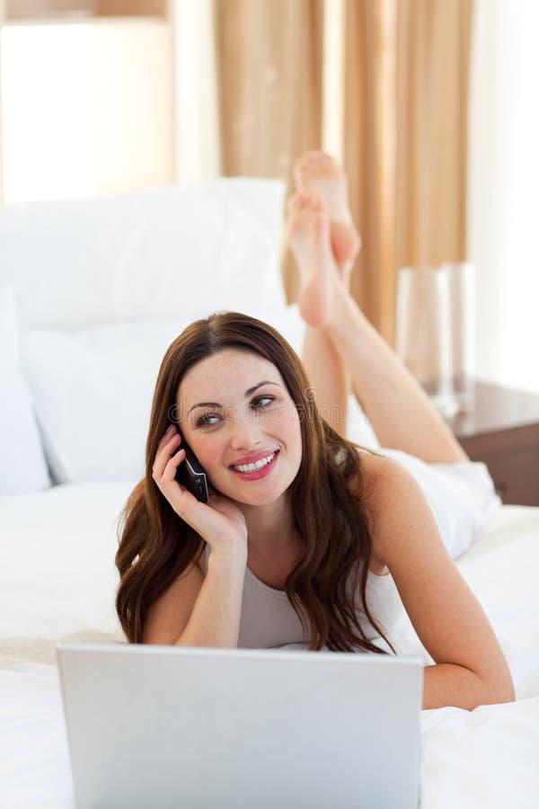 Download Mulher Alegre No Telefone Usando Seu Portátil Que Encontra-se Na Cama Imagem de Stock - Imagem de ocasional, home: 12813393