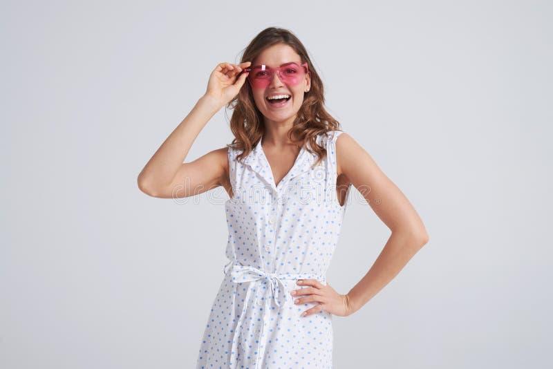 Mulher alegre nos óculos de sol que levantam no fundo foto de stock royalty free