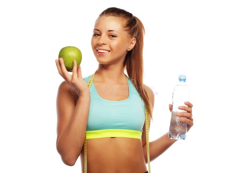 A mulher alegre nos esportes veste com maçã e uma garrafa da água, isolada sobre o fundo branco imagens de stock