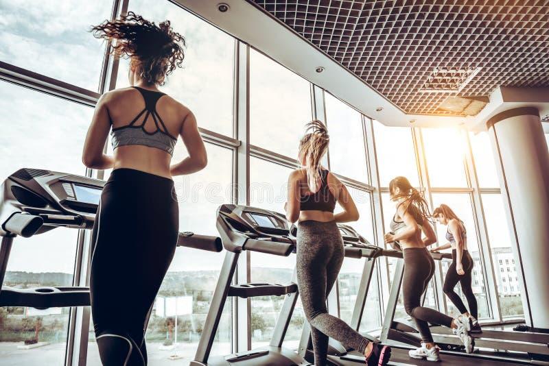 Mulher alegre nova bonita no sportswear que corre na escada rolante no gym com outras mulheres imagens de stock royalty free
