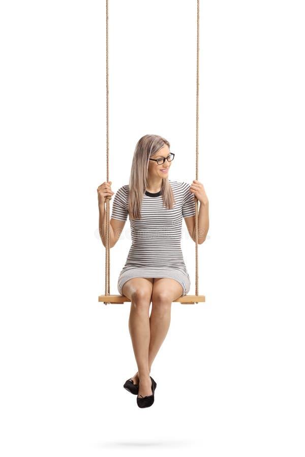 Mulher alegre nova que senta-se em um balanço fotos de stock royalty free