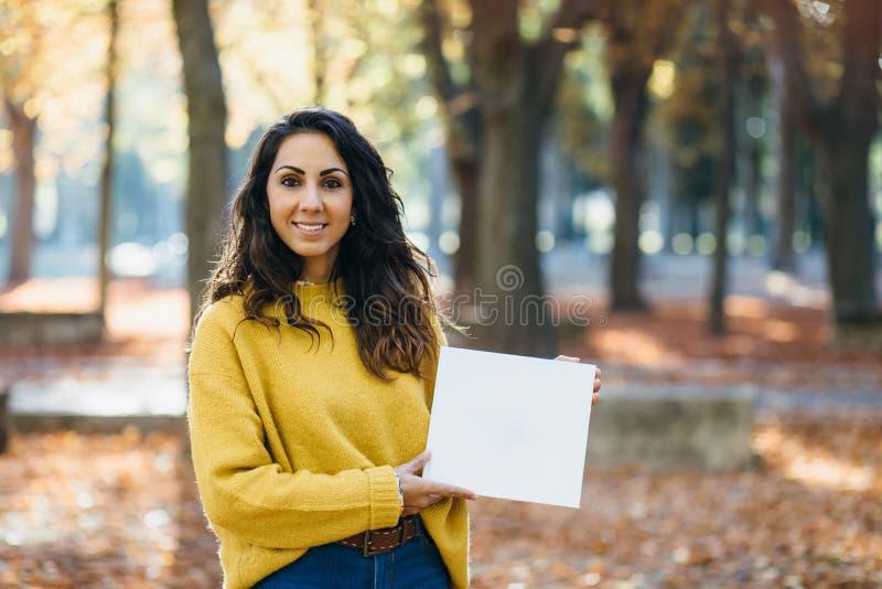 Mulher alegre ocasional que mostra o papel branco do espaço da cópia foto de stock