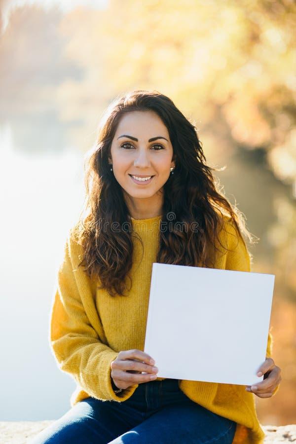 Mulher alegre ocasional que mostra o papel branco do espaço da cópia fotos de stock