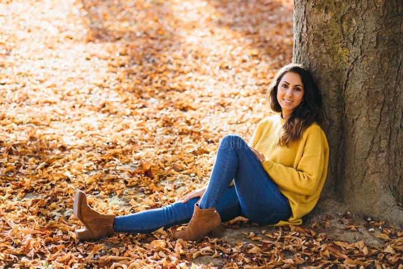Mulher alegre ocasional que relaxa no outono foto de stock royalty free