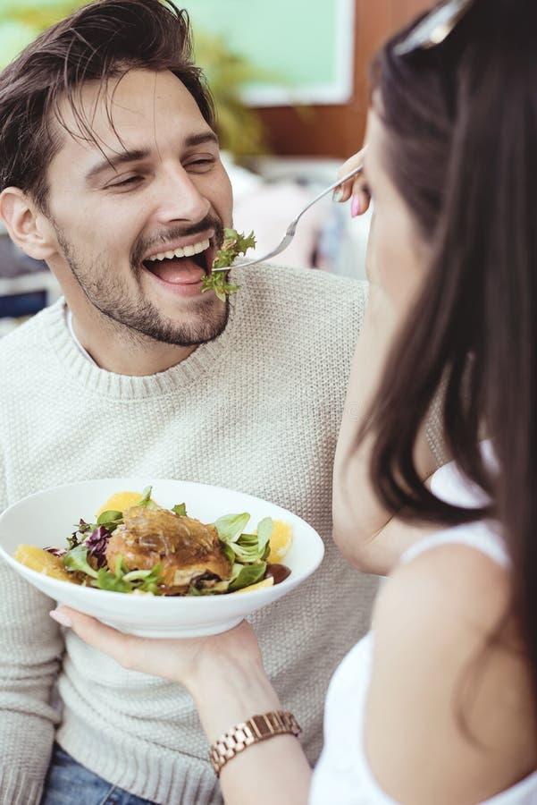 Mulher alegre que alimenta seu noivo considerável foto de stock royalty free
