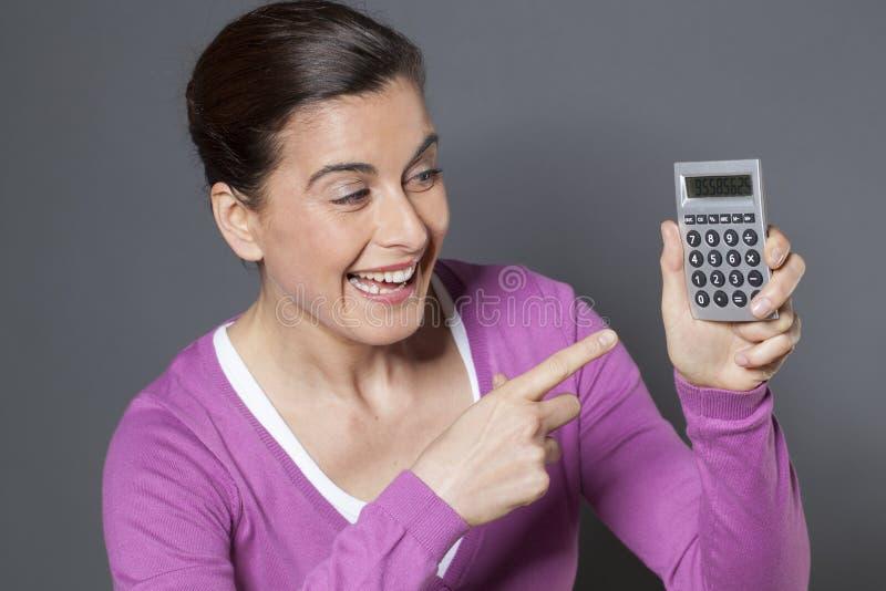 Mulher alegre que aponta na calculadora fotos de stock royalty free