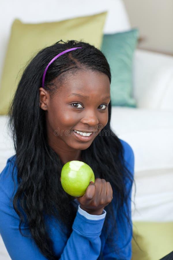 Mulher alegre que come uma maçã foto de stock