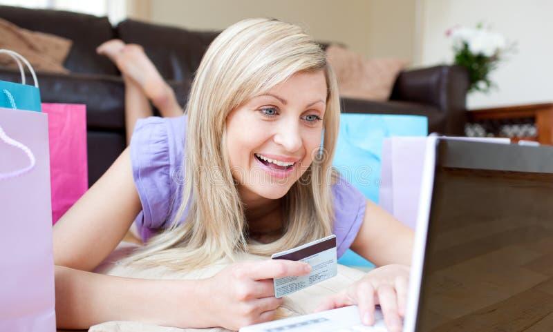Mulher alegre que compra em linha encontrando-se no assoalho fotografia de stock royalty free