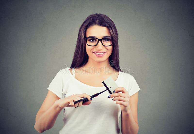 Mulher alegre que corta o cartão de crédito que paga para fora todos os débitos fotografia de stock royalty free