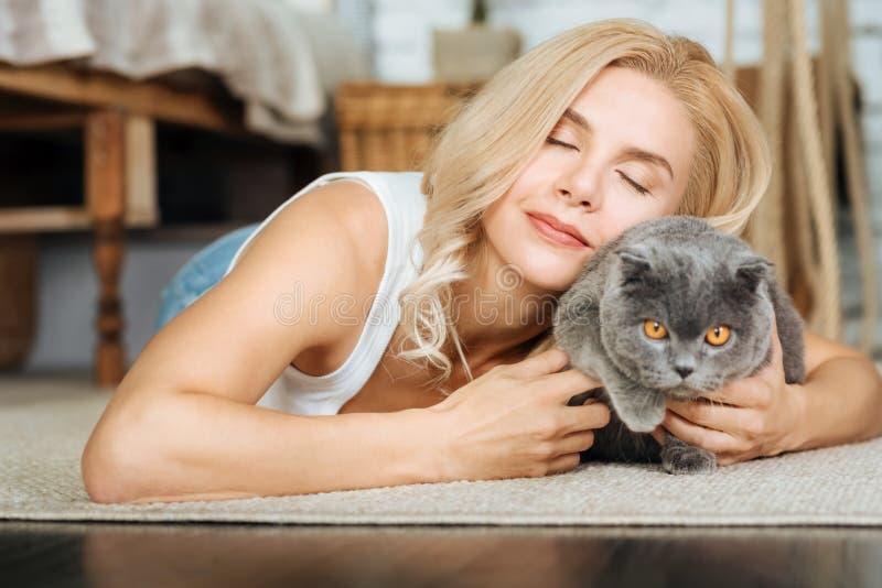 Mulher alegre que encontra-se no assoalho com seu gato imagem de stock