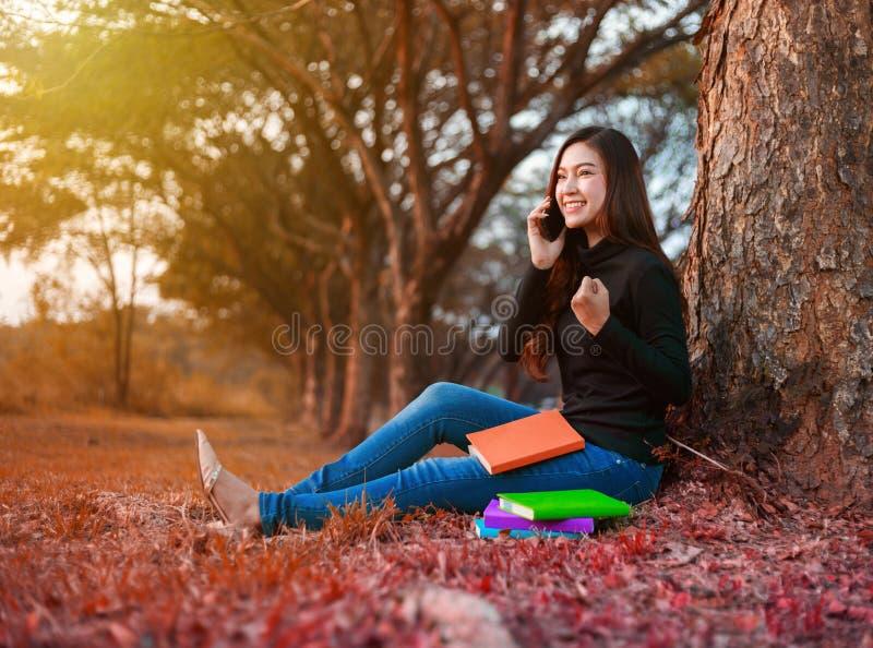 A mulher alegre que fala no telefone celular com mão aumentou no parque imagem de stock