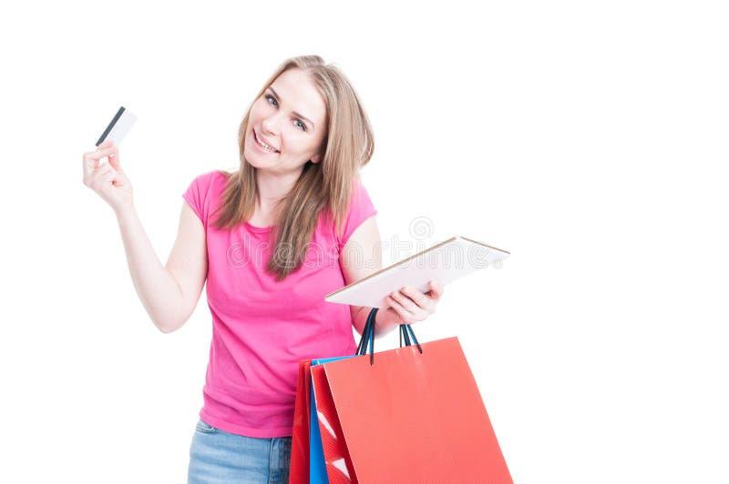 Mulher alegre que faz a compra usando o PC da tabuleta e o cartão de crédito imagens de stock