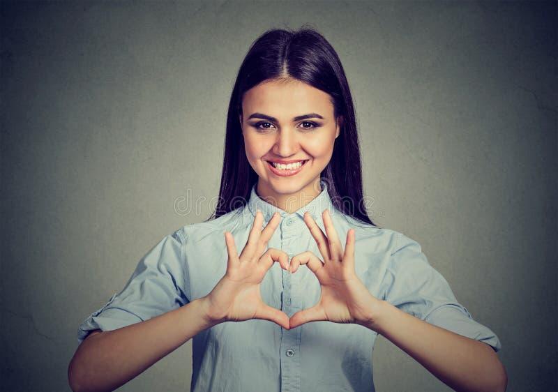 Mulher alegre que faz o sinal do coração com mãos imagens de stock royalty free