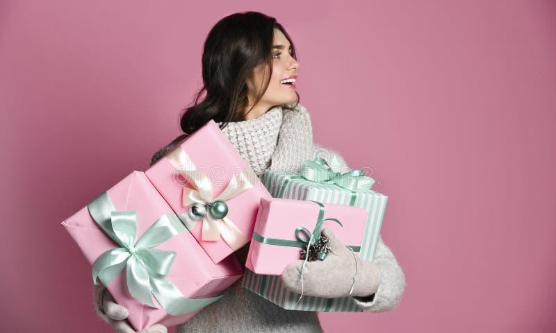 Mulher alegre que guarda muitas caixas com presentes em um fundo cor-de-rosa fotografia de stock royalty free