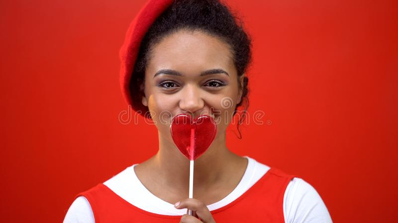 Mulher alegre que guarda a parte dianteira coração-dada forma do pirulito da boca no fundo vermelho imagens de stock royalty free