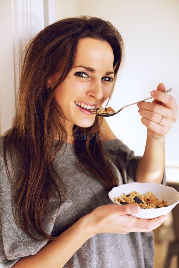 Mulher alegre que guardara uma bacia de cereal imagem de stock