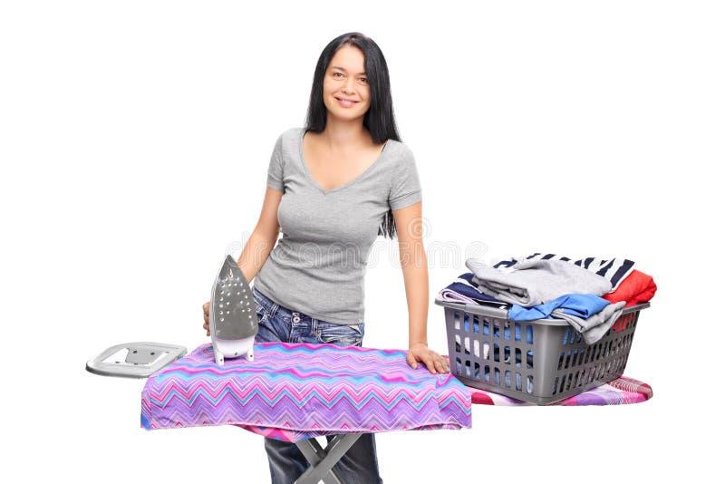 Mulher alegre que levanta atrás de uma tábua de passar a ferro imagem de stock
