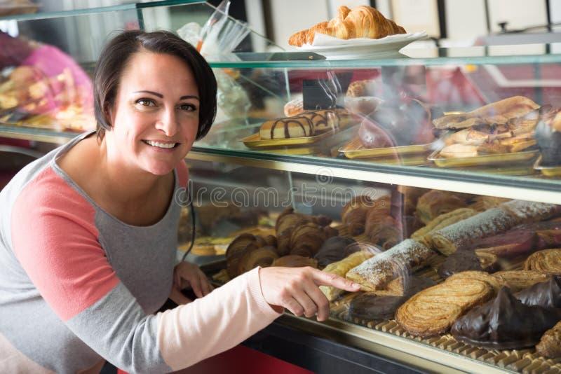 Mulher alegre que olha na pastelaria imagens de stock