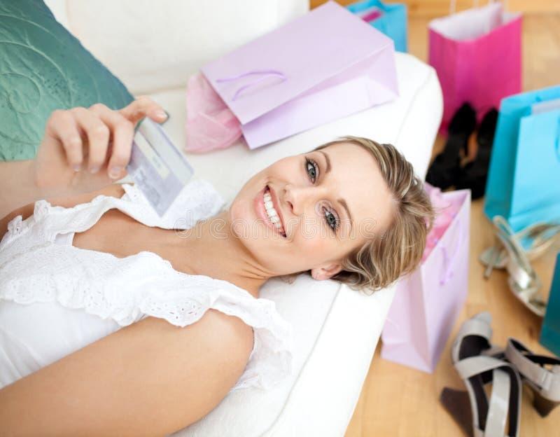 Mulher alegre que prende um cartão de crédito imagens de stock