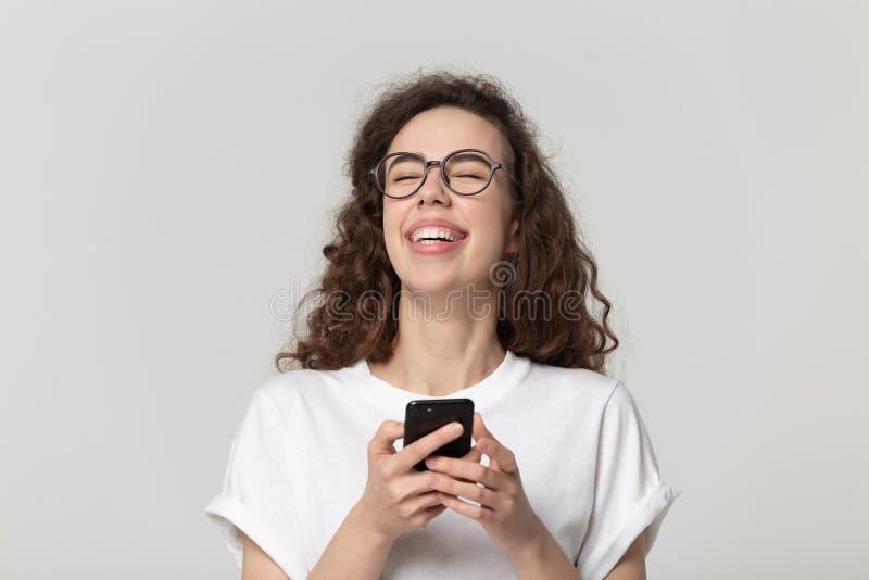 Mulher alegre que ri usando o tiro do estúdio dos apps do smartphone imagem de stock royalty free