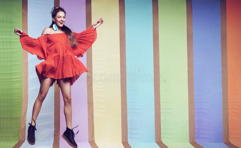 Mulher alegre que salta no vestido alaranjado em botas pretas foto de stock royalty free