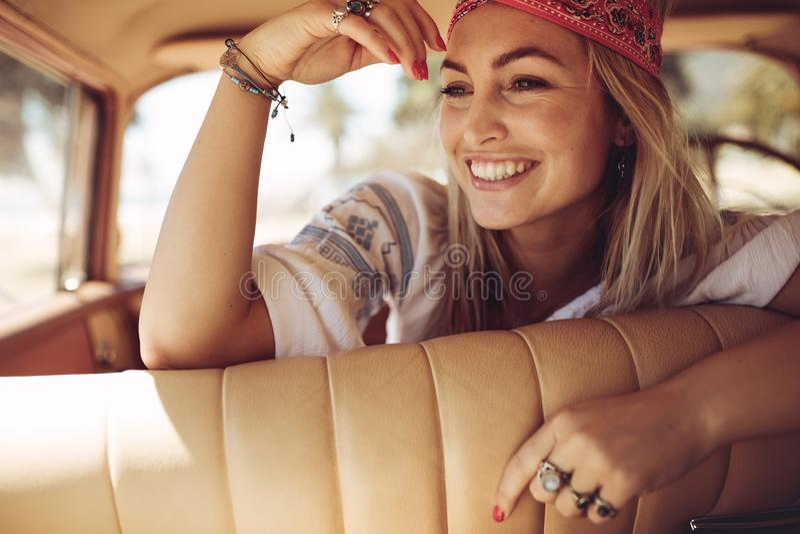 Mulher alegre que senta-se em um carro fotos de stock
