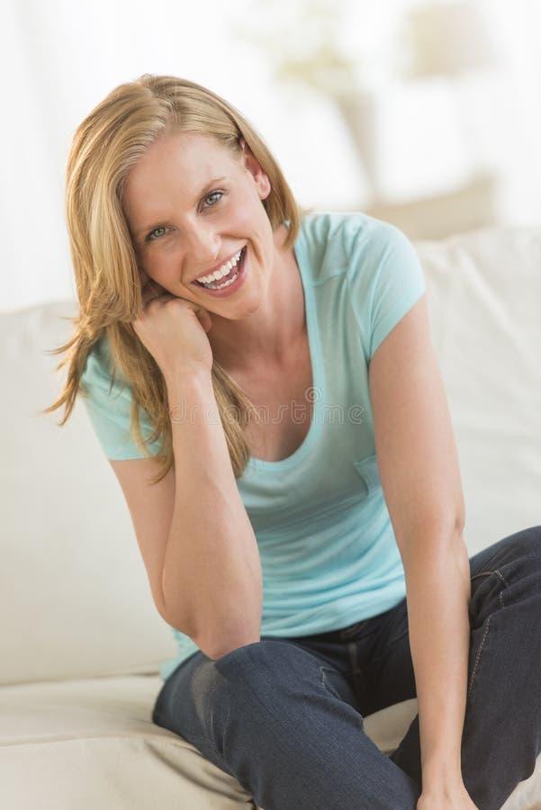 Mulher alegre que senta-se no sofá fotografia de stock royalty free