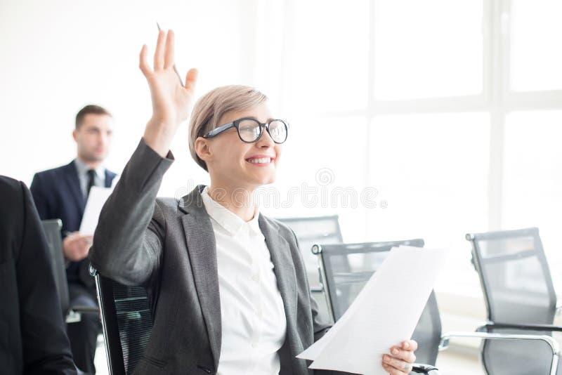 Mulher alegre que tem a pergunta na reunião de negócios fotografia de stock