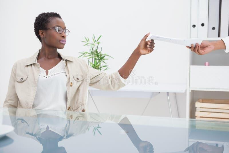 Mulher alegre que toma o papel de seu colega imagem de stock