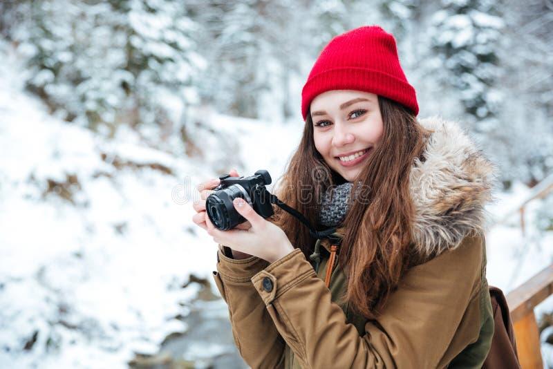 Mulher alegre que usa a câmera da foto e tomando imagens no inverno imagens de stock