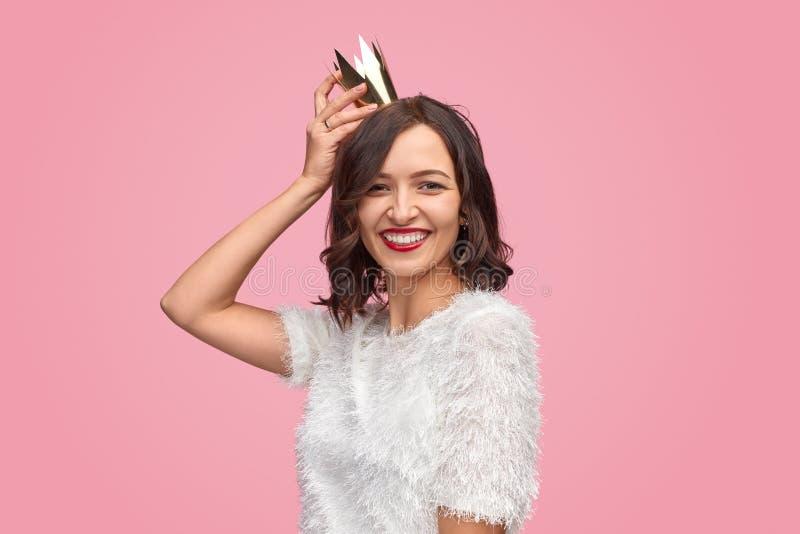 Mulher alegre que veste a coroa brilhante no partido fotografia de stock