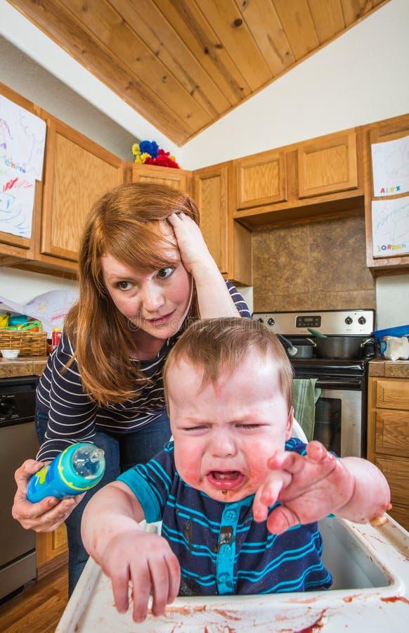 A mulher alimenta o bebê de Gumpy fotografia de stock royalty free