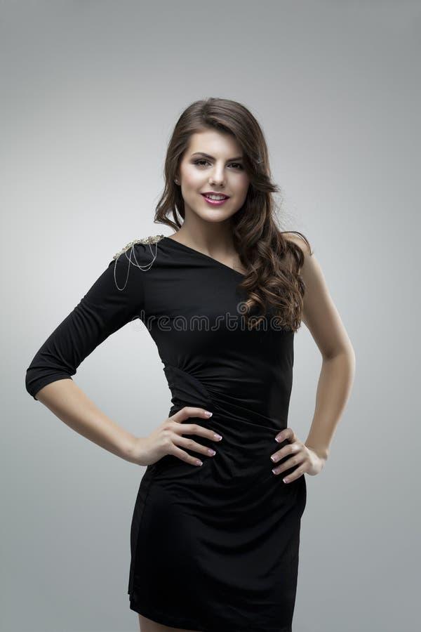 Mulher alta que levanta o vestido preto imagem de stock