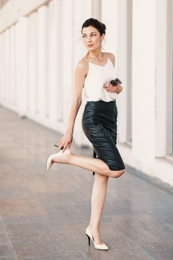 Mulher alta que toca no salto preto em sua sapata nude ao olhar sobre o ombro fora fotografia de stock royalty free