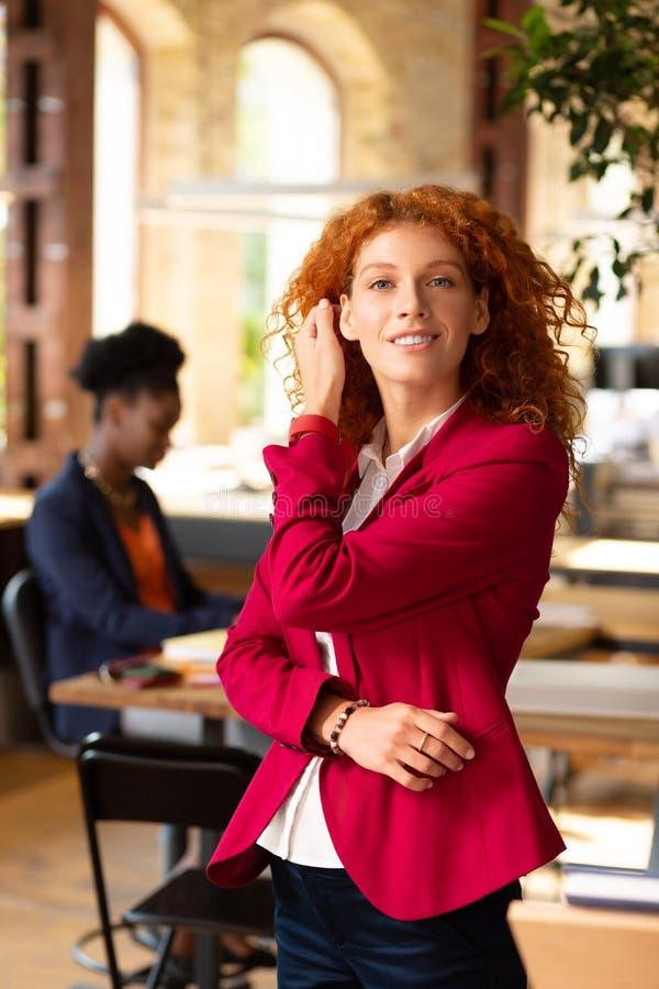 Mulher amaldiçoada com cabelos bruscos parados perto de seu colega imagens de stock