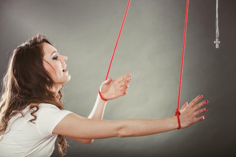Mulher amarrada forçada a rezar Fé falsificada Religião fotografia de stock